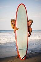 Male and female surfer posing with surfboard