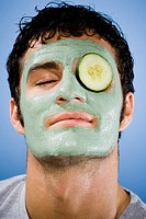Man with mud mask and cucumber slice with closed eyes