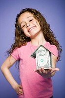 Young girl with a little house made of banknotes