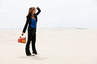 USA, Utah, Little Sahara, young woman holding kettle in desert
