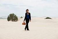 USA, Utah, Little Sahara, young businesswoman walking on desert carrying gas can