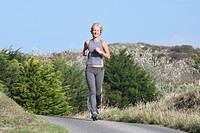 Blonde woman outdoors. Jogging along country road.