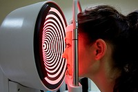Eye examination  Patient having a corneal topography measurement made of her eye  The device at centre projects bright rings onto the eye, which are r...