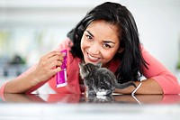 Happy young woman showing her kitten a sachet of cat food