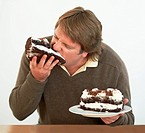 An obese man biting into a piece of cake