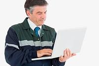 Repairman in coveralls using laptop