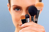 Cropped view of a young woman holding up an assortment of makeup brushes