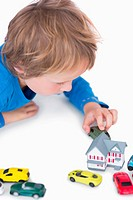 Close_up of boy playing with playhouse and toy cars