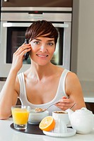 Woman having breakfast while on the phone