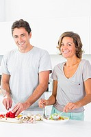 Happy couple preparing salad