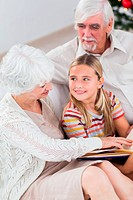 Grandparents with granddaughter reading