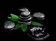 blak spa stones with leaf and water drops.