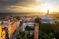 Setting sun behind the Sokollu Mehmet Pasha mosque minaret with golden glow on houses and Marmara Sea Istanbul