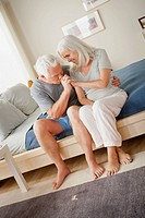 Senior couple sitting on bed in close embrace