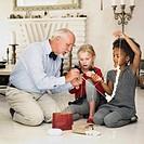 Older man and girls stringing popcorn