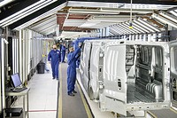 Workers inspecting cars in factory