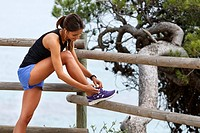 Runner tying laces on wooden fence