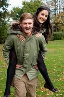 Man carrying girlfriend in park