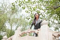 Chinese businesswoman standing on bridge