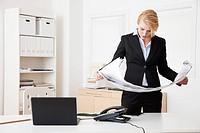 Caucasian businesswoman reading blueprints in office