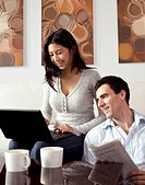 Couple relaxing together with newspaper and laptop