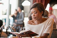 African American woman reading book in cafe