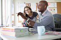Coworkers reviewing work on desktop computer.