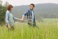Middle_aged couple walking in high grass holding hands.
