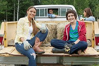 Teen and pre_teen children sitting on tailgate of dad´s truck.