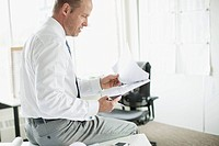 Middle_aged businessman reviewing report in office.