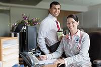 Portrait of medical professionals at office desk.