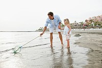 Father with daughter playing with fishnet on beach