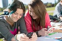 Teenage girls texting on smart phones outdoors.