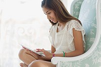 Pretty preteen using pc tablet at home.