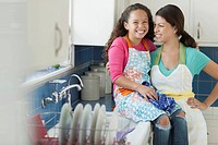 Mother with arm around young daughter in kitchen.