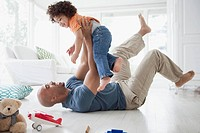 Father lying on the floor and lifting toddler son.
