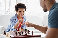 Father and son challenging each other in chess game.