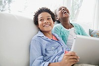 Sister and brother having a laugh browsing pc tablet.