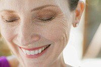 Close_up of woman laughing with eyes closed.