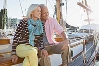Senior couple sitting on sailboat.