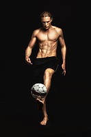A young man balancing a soccer ball on his foot over a black backgroud