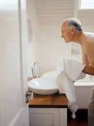 An elderly man at the bathroom sink