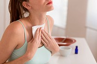 Woman applying a poultice on the thyroid.