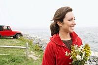 Woman holding bouquet of flowers near the ocean