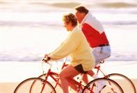 Couple Cycling Along Shore