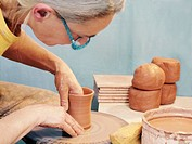 Potter spinning clay on pottery wheel