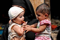 Muslim women stand in a queue with their children at a pulse polio drive at Baiganwadi ; Govandi ; Bombay now Mumbai ; Maharashtra ; India