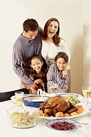 Portrait of a family posing behind a dinner table at Thanksgiving