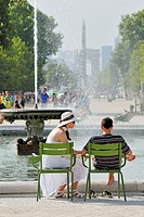 Paris, France Jardin des Tuileries. Young attractive couple relaxing on a very hot day