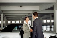 Business people shaking hands in a car park